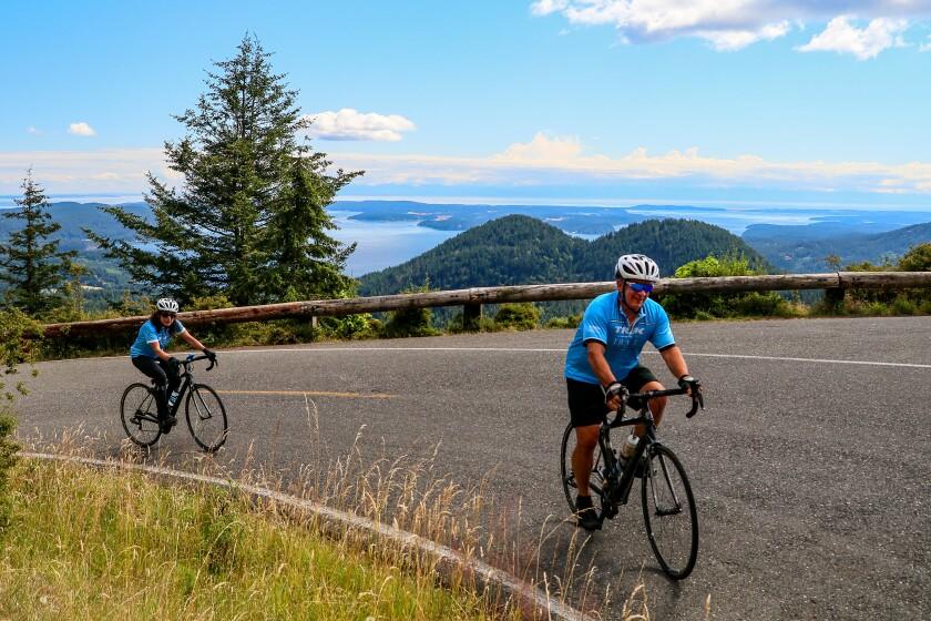 A couple climbs a hill overlooking Washington's coastal islands.