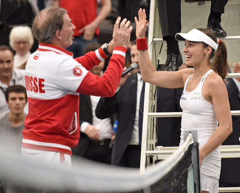Martina Hingis of Switzerland celebrates together with Swiss team captain Heinz Guenthardt after winning her doubles match during the Fed Cup World Group first round tennis match between Germany and Switzerland at the Leipzig Fair in Leipzig, Germany, Sunday, Feb. 7, 2016. (AP Photo/Jens Meyer)