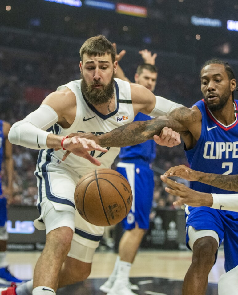 LOS ANGELES, CALIF. -- SATURDAY, JANUARY 4, 2020: Memphis Grizzlies center Jonas Valanciunas, left, and forward Ja Morant, right, battle Clippers forward Kawhi Leonard for a rebound during the first half at the Staples Center in Los Angeles, Calif., on Jan. 4, 2020. (Allen J. Schaben / Los Angeles Times)