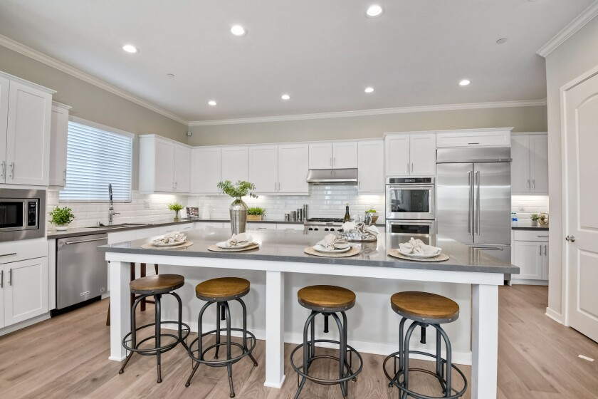 New Pointe Communities' home has an open kitchen, stainless-steel dual ovens and built-in 42-inch refrigerator.