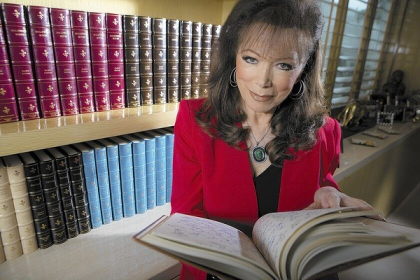 Author Jackie Collins holds one of dozens of bound, handwritten manuscripts in her library