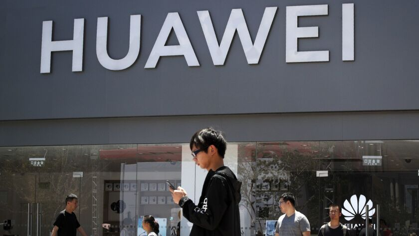 People walk past a Huawei retail store in Beijing, Sunday, June 30, 2019. Once again, Presidents Don
