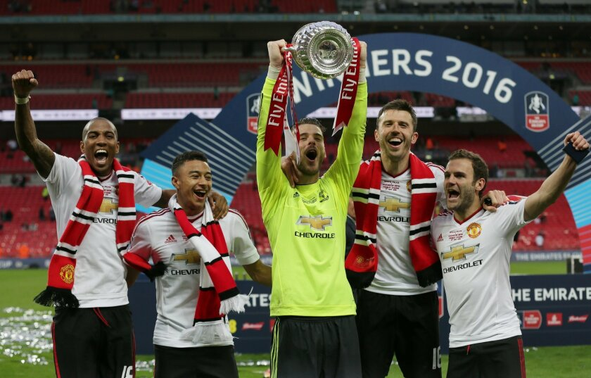 Manchester United's goalkeeper David de Gea celebrates with the trophy after winning the English FA Cup final soccer match against Crystal Palace at Wembley Stadium, London on Saturday May 21, 2016. Manchester United won the match 1-2. (AP Photo/Tim Ireland)
