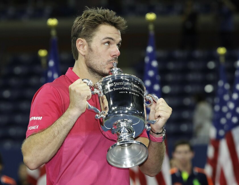 Stan Wawrinka, of Switzerland, kisses the championship trophy after beating Novak Djokovic, of Serbia, to win the men's singles final of the U.S. Open tennis tournament, Sunday, Sept. 11, 2016, in New York. . (AP Photo/Darron Cummings)