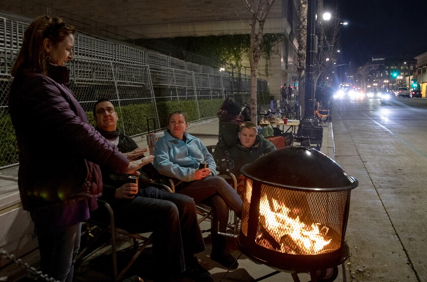 Denise Koehnlein of Phoenix, left, stays warm by the fire while chatting with Mark Breiling, Quisha Ryan and Christian Ryan.