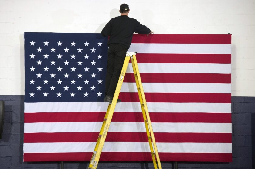 A worker hangs an American flag before a primary night party in New Hampshire in February.
