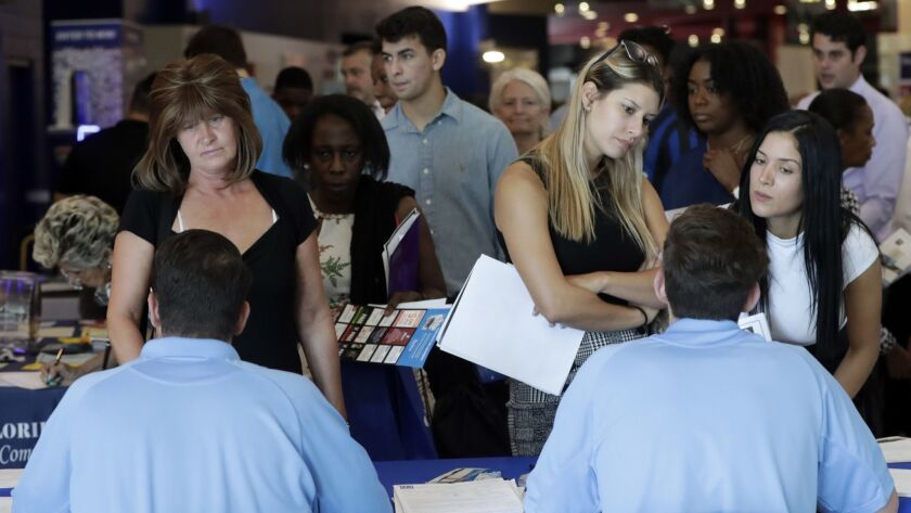 FILE- In this June 21, 2018, file photo, job applicants talks with representatives from Aldi at a jo