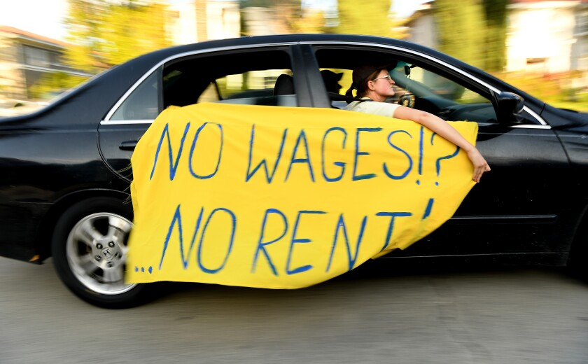 """A protester drives by with a sign saying """"No wages, no rent."""""""