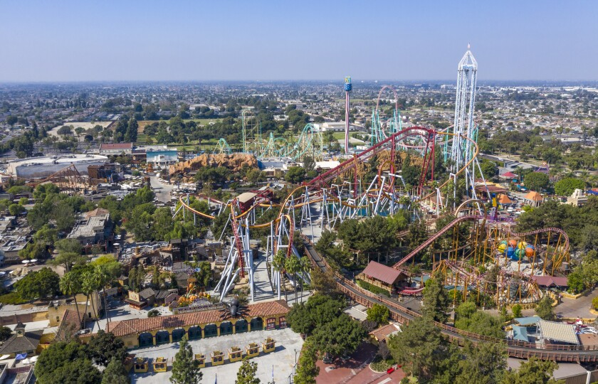 An aerial view of multiple roller coasters at a theme park.