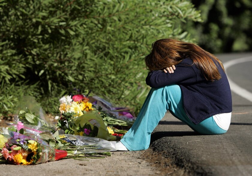 Emily Heil, 16, mourned at the site on La Granada near Rambla de las Flores in Rancho Santa Fe where Torrey Pines High School student Alex Capozza, 17, was killed in a car crash early Sunday. The driver is being held at Juvenile Hall and is facing felony charges.