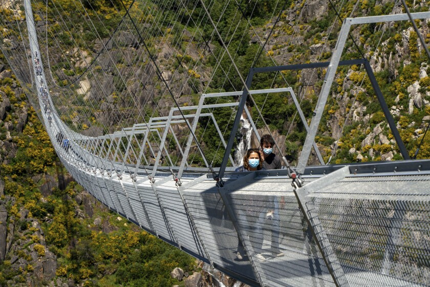 People walk across a narrow footbridge suspended across a river canyon, which claims to be the world's longest pedestrian bridge, in Arouca, northern Portugal, Sunday, May 2, 2021. The Arouca Bridge inaugurated Sunday, offers a half-kilometer (almost 1,700-foot) walk across its span, some 175 meters (574 feet) above the River Paiva. (AP Photo/Sergio Azenha)
