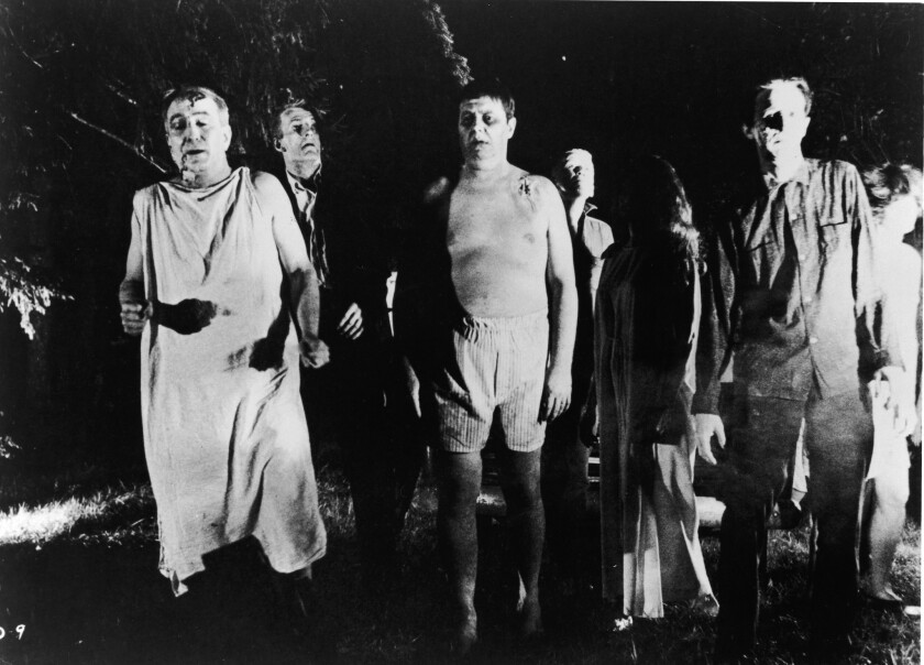 """""""Zombies"""" walk through a field in the night in a still from the film  """"Night Of The Living Dead."""""""