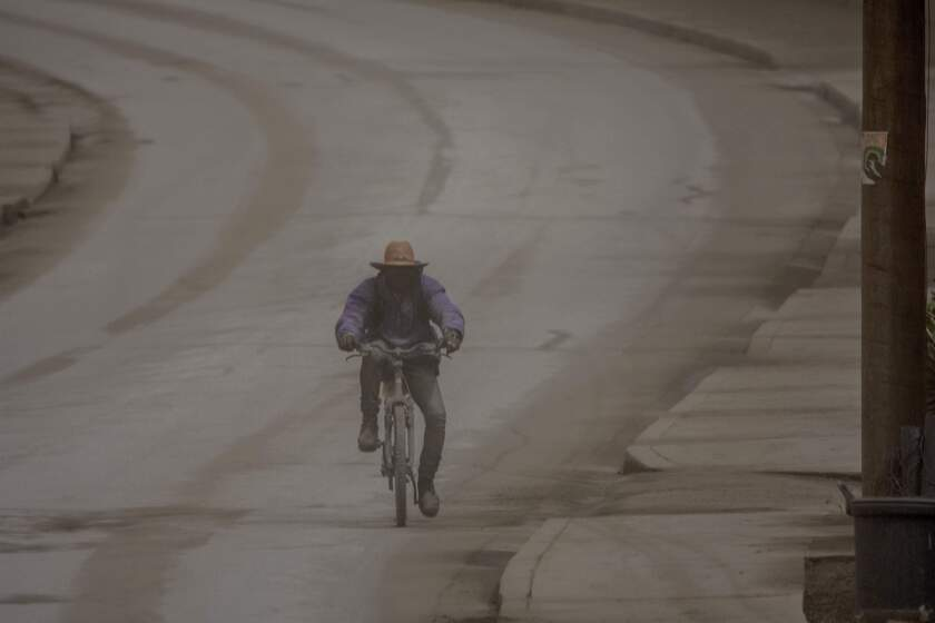 A man rides his bicycle along the main Black Rock road, covered with ash coming from the eruption of La Soufriere volcano in the neighboring island of St. Vincent, on the outskirts of Bridgetown, Barbados, Sunday, April 11, 2021. (AP Photo/Chris Brandis)