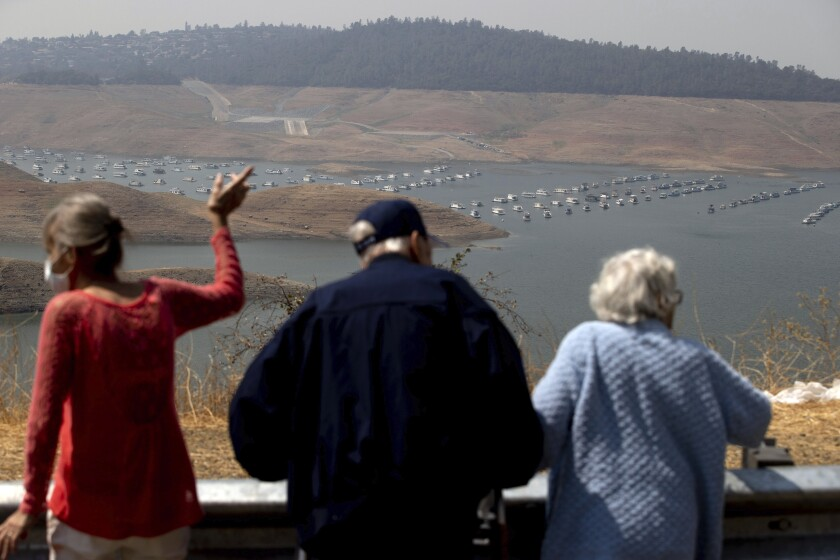 FILE - In this Aug. 22, 2021, file photo, visitors look out over Lake Oroville as water levels remain low due to continuing drought conditions in Butte County, Calif. Californians failed to significantly cut back their water consumption in July, state officials announced Tuesday, Sept. 21, 2021, foreshadowing some difficult decisions for Gov. Gavin Newsom's administration as an historic drought lingers into the fall. (AP Photo/Ethan Swope, File)