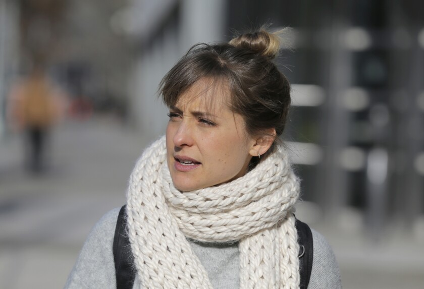A picture of a woman outdoors wearing a white knit scarf