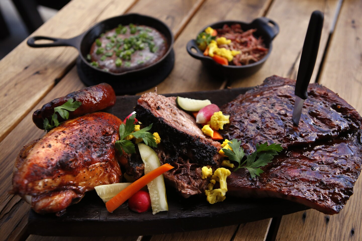 Round out a combo platter of smoked meats with hoe cake, a buttery corn bread dish, and a side of pulled pork at Barrel & Ashes. Jonathan Gold's 101