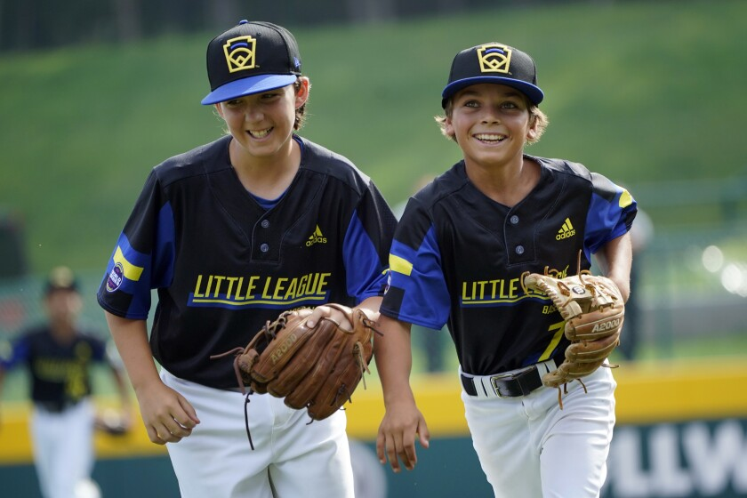 Torrance, Calif.'s Dominic Golia (18) and pitcher Xavier Navarro (7) smile as the run off the field after Navarro caught a line drive back to the mound off the bat of Hamilton, Ohio's Kaleb Harden during the third inning of a baseball game at the Little League World Series in South Williamsport, Pa., Sunday, Aug. 22, 2021. (AP Photo/Tom E. Puskar)