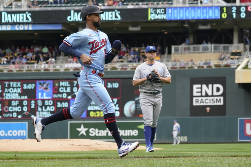 Minnesota Twins' Byron Buxton, left, jogs home on a sacrifice fly by Luis Arraez off Kansas City Royals pitcher Kris Bubic, right, in the first inning of a baseball game, Sunday, Sept. 12, 2021, in Minneapolis. (AP Photo/Jim Mone)