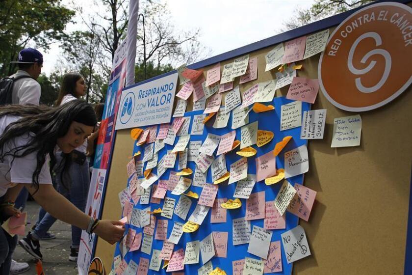 """Una mujer deja un mensaje por la celebración del """"Día Mundial del Cáncer"""" hoy, sábado 4 de febrero de 2017, en la explanada del Monumento a los Niños Héroes, en Ciudad de México (México). México reporta cada año unos 190.000 nuevos casos de cáncer y fallecen 80.000 personas por ese padecimiento, informó la Secretaría de Salud este sábado, Día Mundial contra el Cáncer. EFE"""