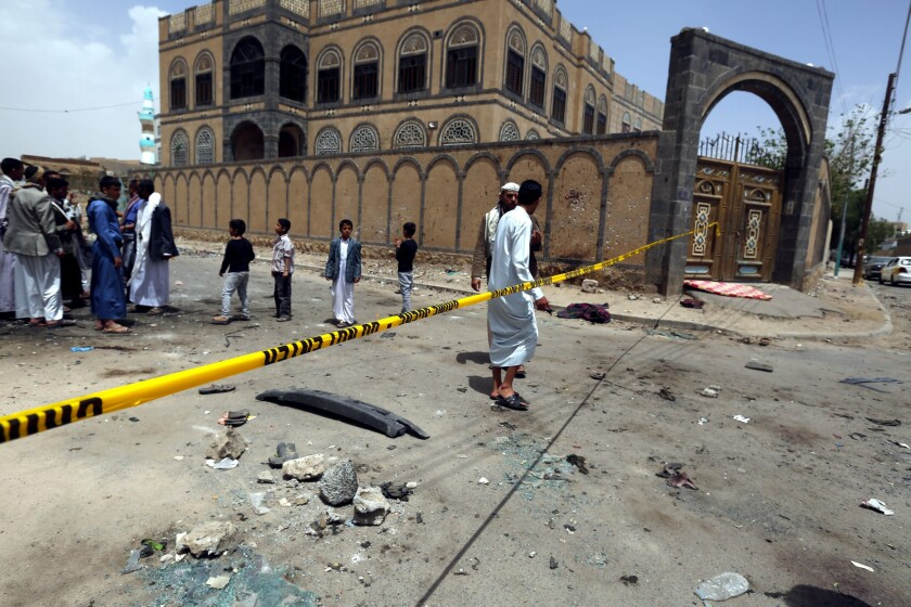 Yemenis and members of the Houthi militia inspect the scene of a suicide attack at a Houthi mosque in Sana'a, Yemen on March 21.