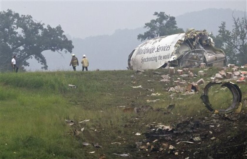 Fire crews investigate where a UPS cargo plane lies on a hill at Birmingham-Shuttlesworth International Airport after crashing on approach, Wednesday, Aug. 14, 2013, in Birmingham, Ala. Toni Herrera-Bast, a spokeswoman for Birmingham's airport authority, says there are no homes in the immediate area of the crash. (AP Photo/Butch Dill)