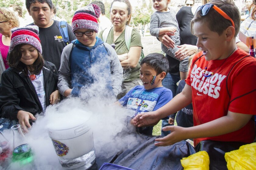 Kids at the Mad Science booth react to the fog created by a dry ice bubble bursting.
