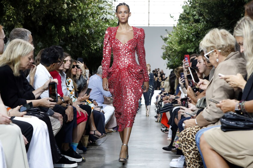 A runway model in a star-spangled red dress by Michael Kors