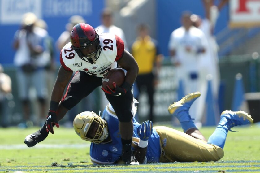 Juwan Washington #29 of the San Diego State Aztecs breaks a tackle by Martin Andrus Jr. #44 of the UCLA Bruins during the first half of a game on Sept. 7, 2019 in Los Angeles, California.