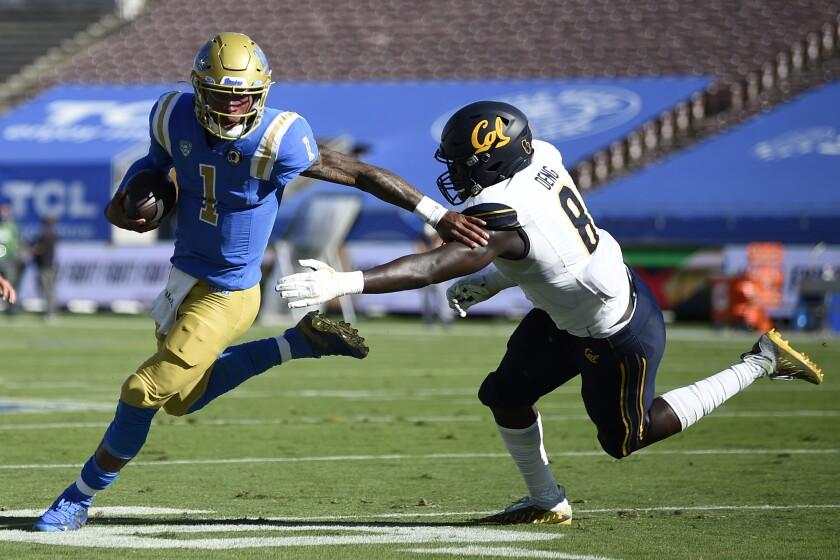 UCLA quarterback Dorian Thompson-Robinson runs the ball while California linebacker Kuony Deng defends.