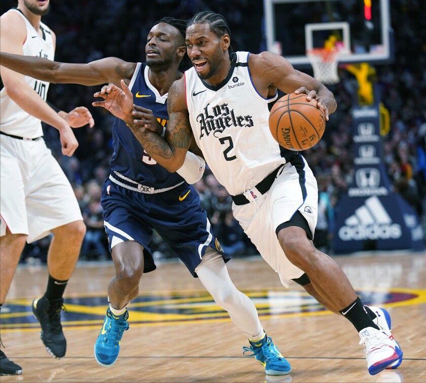 Los Angeles Clippers forward Kawhi Leonard (2) drives past Denver Nuggets forward Jerami Grant (9) during the second quarter of an NBA basketball game, Sunday, Jan. 12, 2020, in Denver. (AP Photo/Jack Dempsey)