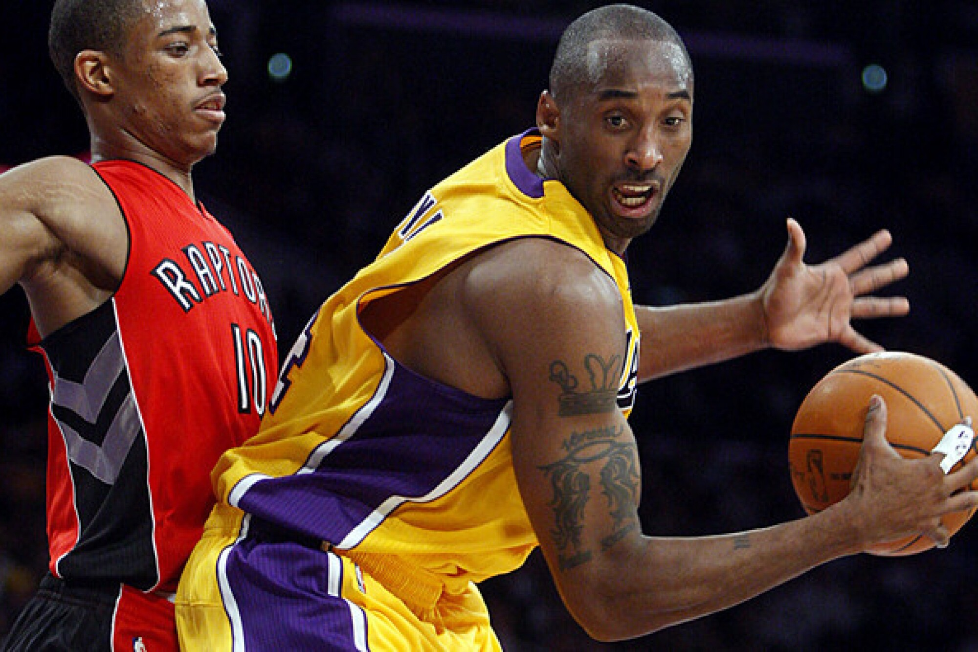 Lakers guard Kobe Bryant receives a pass while guarded by Raptors guard DeMar DeRozan.