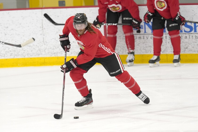 Chicago Blackhawks' Duncan Keith handles the puck during an NHL hockey training camp practice Monday, Jan. 4, 2021, in Chicago. (AP Photo/Charles Rex Arbogast)