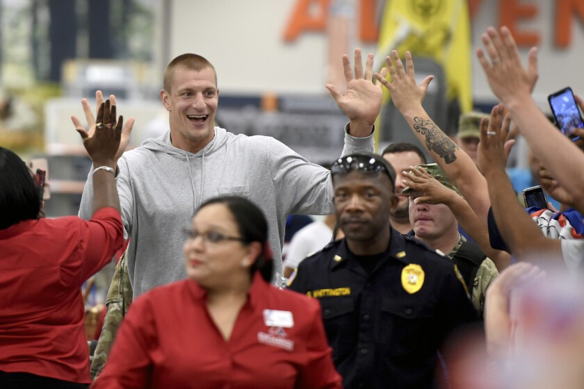 Former New England Patriots tight end Rob Gronkowski greets fans as he arrives at a department store on June 26.