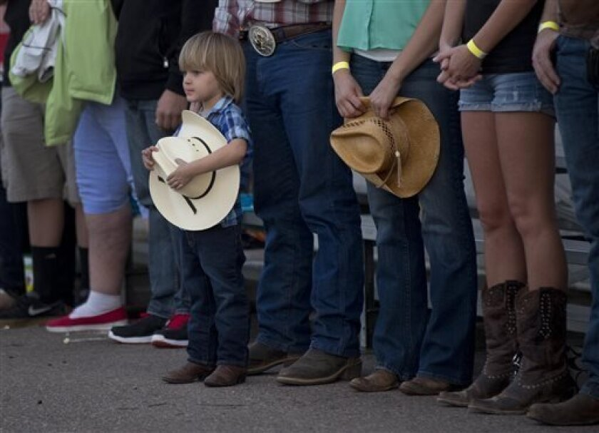 A young boy holds his hat as he and others stand for the national anthem before the start of the Prescott Frontier Days Rodeo, Wednesday, July 3, 2013 in Prescott, Ariz. A mile-high city about 90 miles northwest of Phoenix, Prescott remains a modern-day outpost of the pioneer spirit. It's that spirit that will guide officials as they navigate the days ahead and figure out how to honor the elite Hotshot firefighters who died in a nearby wind-driven wildfire that is still burning. (AP Photo/Julie