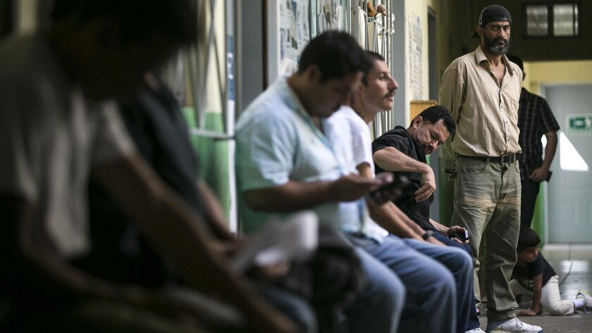 Immigrants seeking a way into the United States wait to speak to attorneys at a two-day clinic at a shelter in Tijuana.