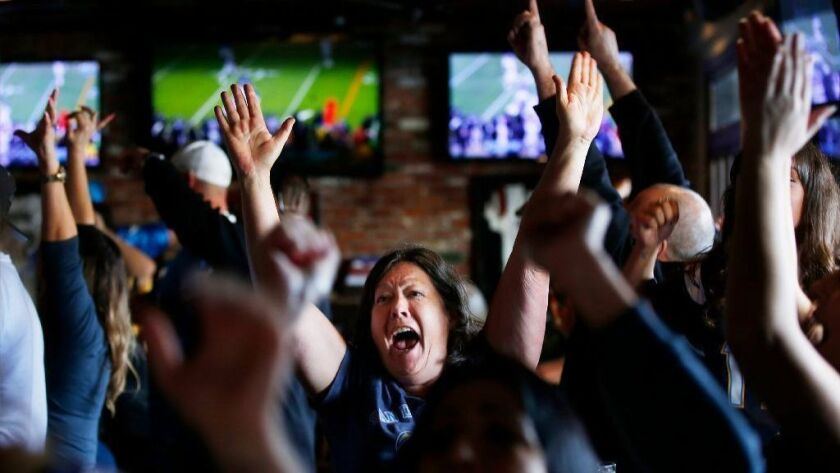 Chargers fans, including Teri Brown, center, celebrate at McGregor's Ale House in Mission Valley as the team beat the Ravens in a wildcard playoff game on Jan. 6, 2019.