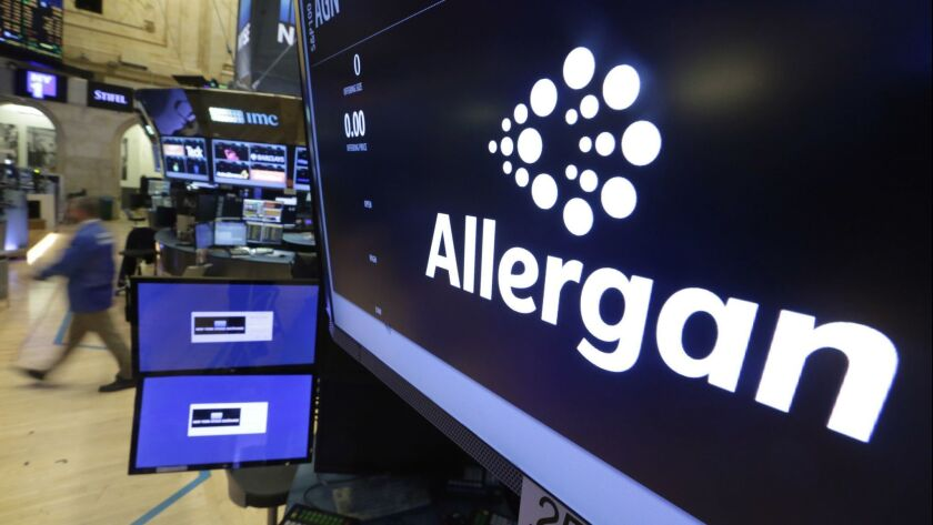 FILE - In this Nov. 23, 2015, file photo, the Allergan logo appears above a trading post on the floo