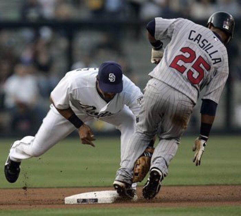 Edgar Gonzalez can't make the tag on the Minnesota Twins' Alexi Casilla, who stretches a left field hit into a double in the first inning at Petco Park Tuesday night.