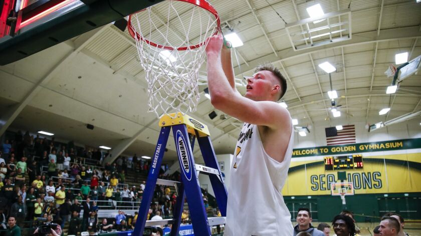 PLNU forward Preston Beverly (1) cuts part of the net following their win over Saint Martin's in the Western Regional Final.