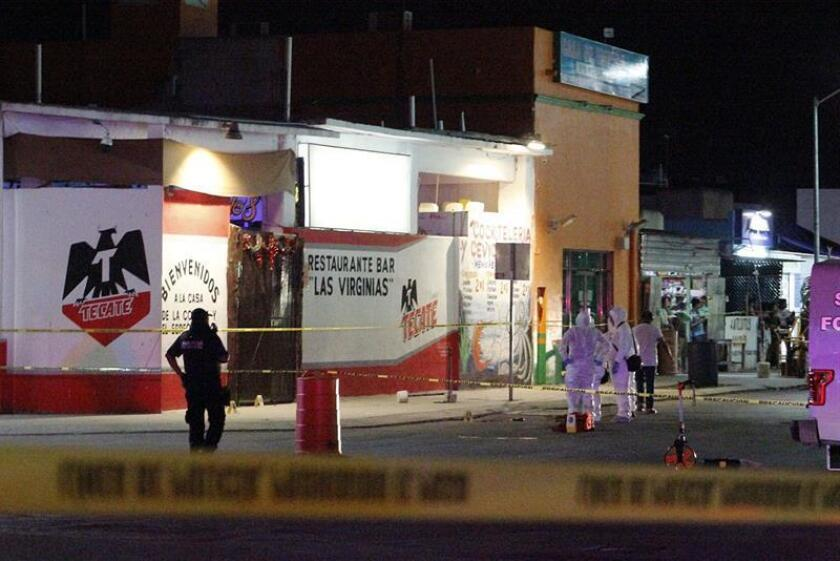 Investigators collect evidence outside a bar in Playa del Carmen, Mexico, where seven people were fatally shot on Sunday, Jan. 6. EFE-EPA