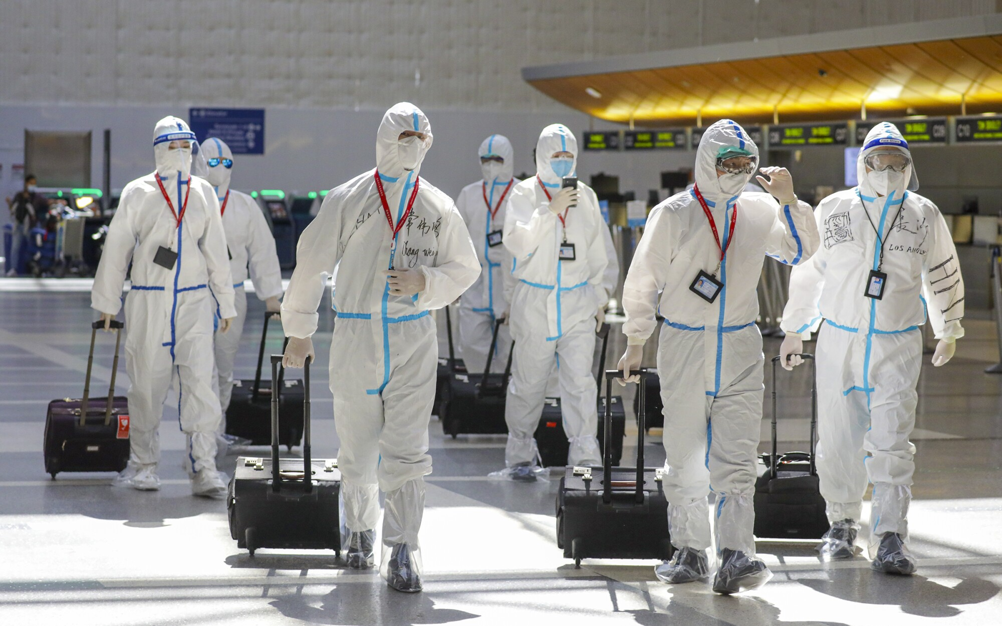 A flight crew in full biohazard suits at Tom Bradley Terminal.