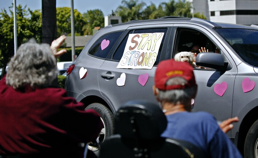 Seniors from Huntington Terrace Senior Living wave at a van with a message as the Sycamore Creek Community Charter School Senior Cheer Parade drives by their location on the 18800 block of Florida Street in Huntington Beach on Saturday.