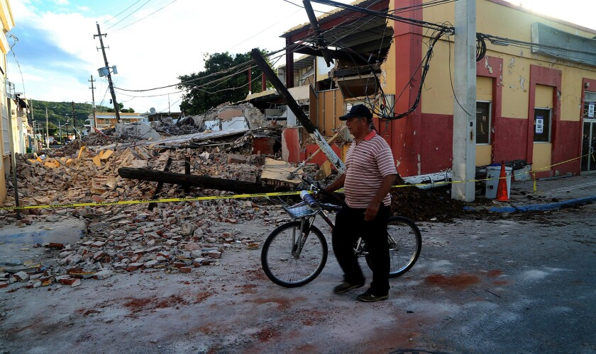 A man walks by a damaged building in the town of Guayanilla on the southern coast of Puerto Rico on Jan. 9.