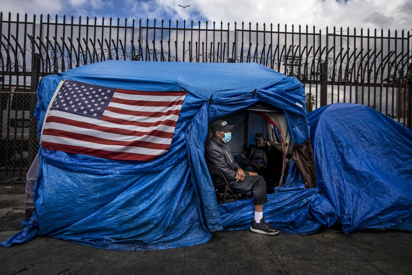 Two men in a tent decorated with an American flag.