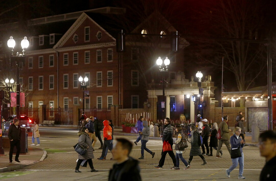 Pedestrians cross Brattle Street in Harvard Square, where several buildings are scheduled for demolition to make way for new development.