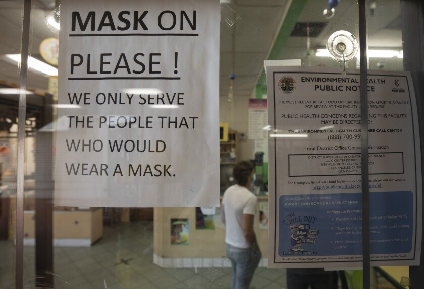 A sign at a Chinatown business reminds customers to wear a mask.