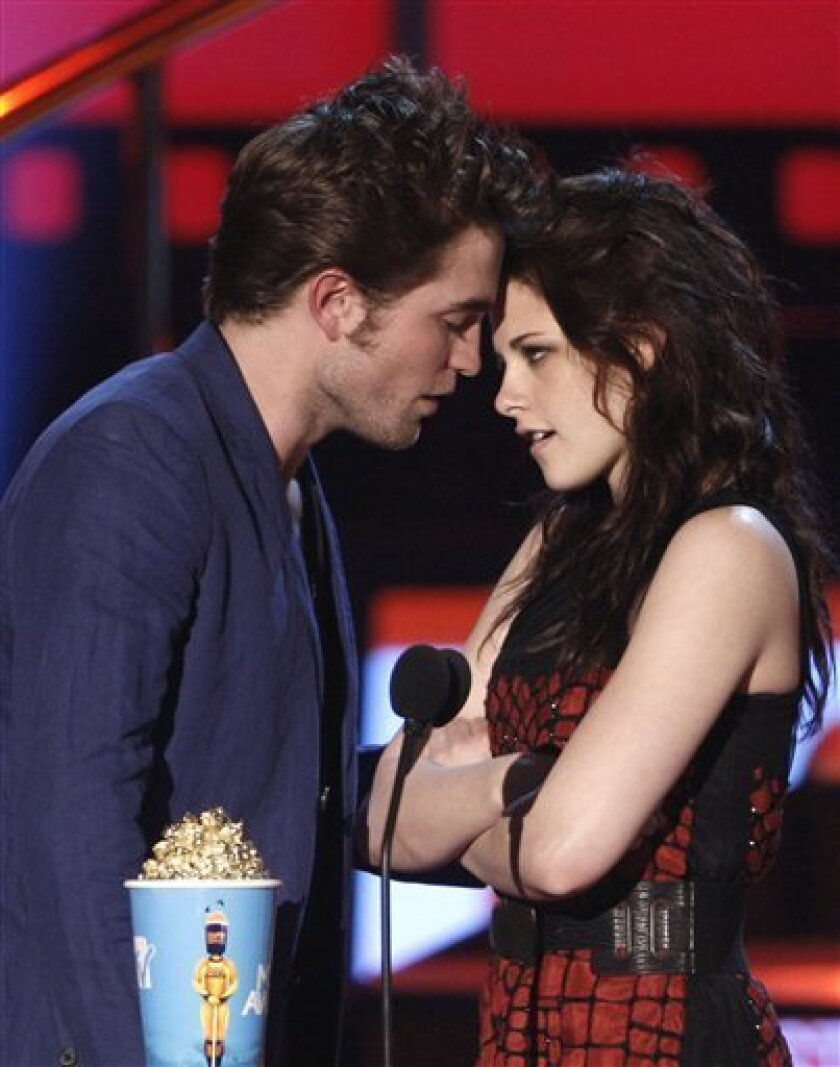 """Robert Pattinson, left, and Kristen Stewart accept the award for best kiss for """" Twilight"""" at the MTV Movie Awards on Sunday May 31, 2009, in Universal City, Calif. (AP Photo/Matt Sayles)"""