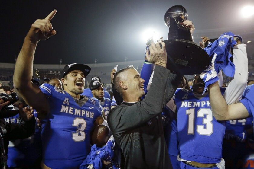 Memphis quarterback Brady White (3) celebrates as coach Mike Norvell lifts the trophy after the Tigers beat Cincinnati on Saturday.