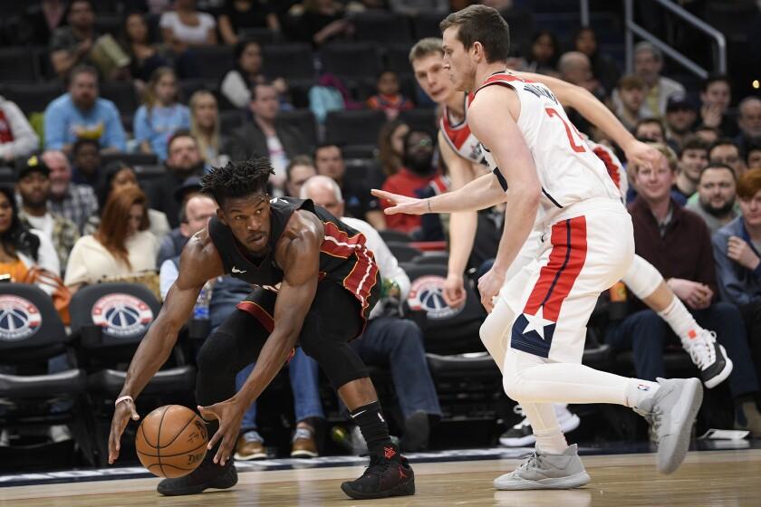 Miami Heat forward Jimmy Butler, left, grabs the ball next to Washington Wizards guard Garrison Mathews, right, during the first half of an NBA basketball game, Sunday, March 8, 2020, in Washington. (AP Photo/Nick Wass)
