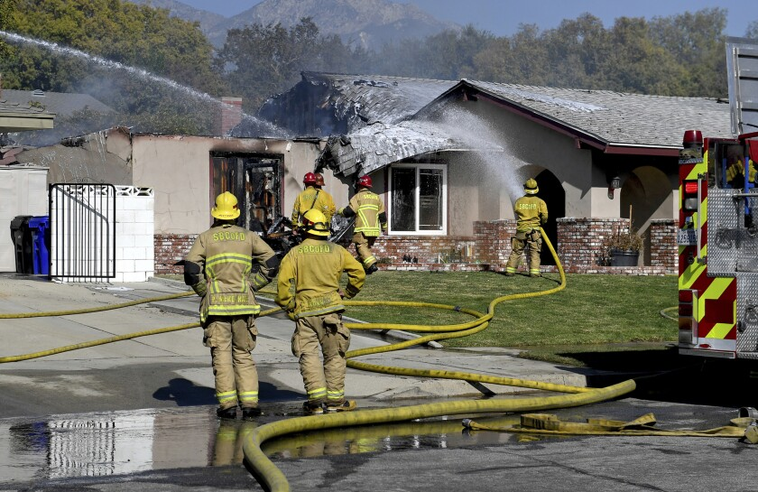 FILE - In this Nov. 7, 2019 file photo, firefighters put out hot spots after a plane crashed into a home in Upland, Calif. According to a preliminary report by the National Transportation Safety Board, the single-engine Cirrus SR22 was getting ready to land at nearby Cable Airport when its wing dipped and the engine stalled. The pilot was killed in the fiery crash Nov. 7 in Upland, about 35 miles (55 kilometers) east of Los Angeles. A father and small child inside the home escaped without injuries. (Jennifer Cappuccio Maher/The Orange County Register via AP, File)